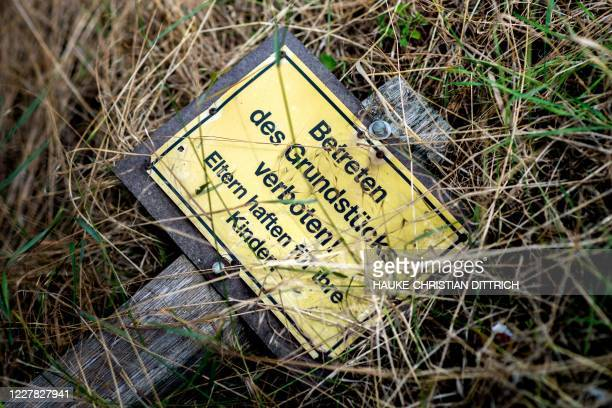"Picture taken on July 29, 2020 shows a sign on the ground reading ""No entry to the property. Parents are liable for their children"", that the police..."