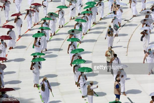 A picture taken on July 29 2020 shows pilgrims holding coloured umbrellas along matching coloured rings separating them as a COVID19 coronavirus...