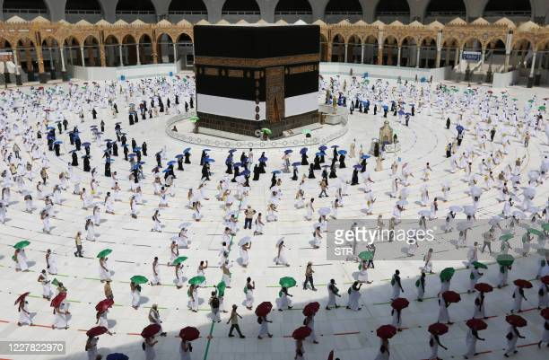 TOPSHOT A picture taken on July 29 2020 shows pilgrims holding coloured umbrellas along matching coloured rings separating them as a COVID19...