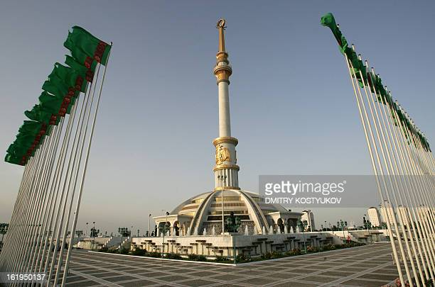 Picture taken on July 3, 2008 shows Turkmen flags flying near the Independence Monument in Ashgabat. Ashgabat contains numerous white-marble...