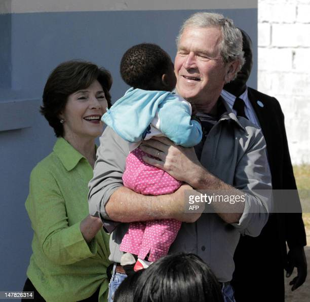 A picture taken on July 3 2012 shows former US President George W Bush flanked by his wife Laura holding a baby at Ngundu health center a clinic...