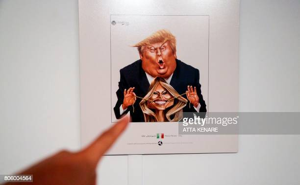 A picture taken on July 3 2017 shows a cartoon of US President Donald J Trump and First Lady Melania Trump on display at an exhibition of the Islamic...