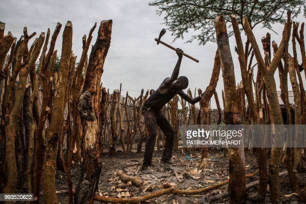 TOPSHOT A picture taken on July 3 shows a man building his home after a World Food Programme plane dropped sacks of maize and sorghum from air in...