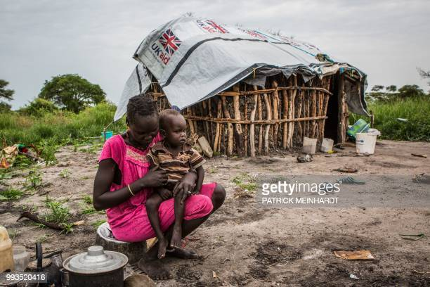TOPSHOT A picture taken on July 3 shows a woman cooking maize and sorghum dropped from air by a World Food Programme plane in Jeich village in Ayod...