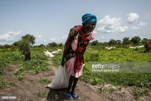TOPSHOT A picture taken on July 3 shows a woman dragging a sack of maize and sorghum dropped from air by a World Food Programme plane in Jeich...