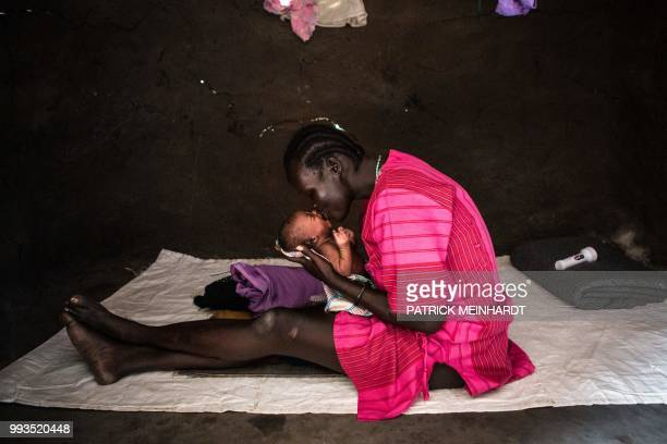 TOPSHOT A picture taken on July 3 shows a woman taking care of her newborn baby at her home after a World Food Programme plane dropped sacks of maize...