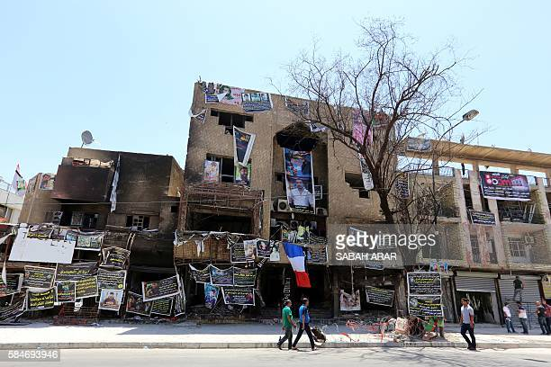 TOPSHOT A picture taken on July 30 2016 shows Iraqis walking past a French national flag hung at the site of the explosion which killed nearly 300...