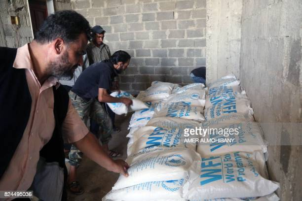 A picture taken on July 30 2017 shows aid packages from the United Nations and the Syrian Arab Red Crescent being delivered to locals in the...