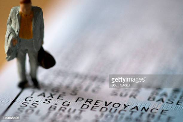 A picture taken on July 31 2012 in Paris shows an illustration made with a figurine set up on a salary slip to illustrate the French CSG France will...