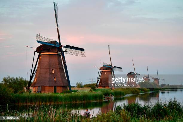 A picture taken on July 31 2017 shows windmills in the village of Kinderdijk southeast of Rotterdam in the Netherlands / AFP PHOTO / TOBIAS SCHWARZ