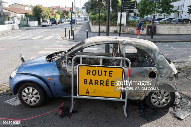 A picture taken on July 4 2018 in the Breil neighborhood of Nantes shows a burned car following clashes between groups of young people and police in...