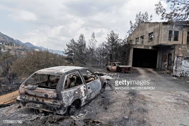 Picture taken on July 4, 2021 shows a destroyed house and car at Eptagonia village on the southern slopes of the Troodos mountains close to Agioi...