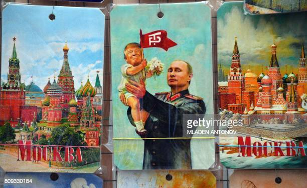 A picture taken on July 5 2017 shows a souvenir kiosk offering among others a drawing depicting Russian President Vladimir Putin holding a baby with...