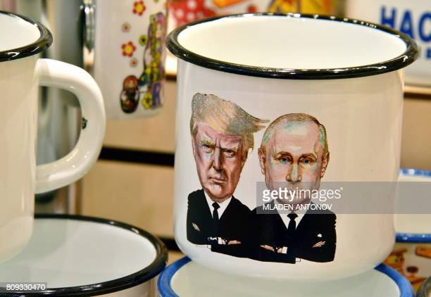 A picture taken on July 5 2017 shows a souvenir shops offering among others cup a tin mug depicting Russian President Vladimir Putin and US President...