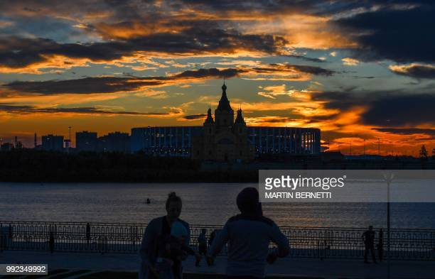 TOPSHOT A picture taken on July 5 2018 shows the Nizhny Novgorod stadium situated behind the cathedral of Alexander Nevskiy in the city of Nizhny...