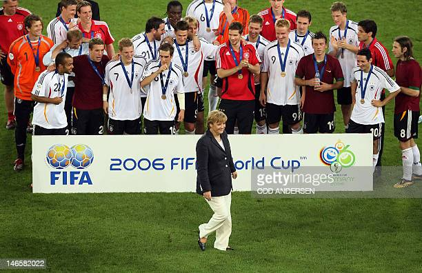 FILES Picture taken on July 6 2006 shows German Chancellor Angela Merkel walking in front of the German team following the medal presentation at the...