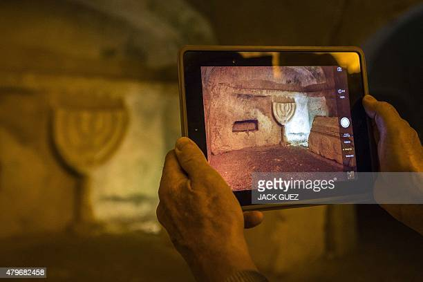 A picture taken on July 6 2015 shows a man using an iPad to take photos at the Jewish burial site at the Beit Shearim National Park north of Israel...