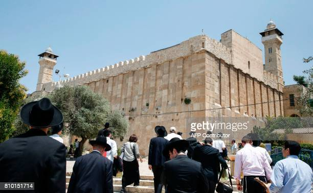 A picture taken on July 7 2017 shows religious Jews and tourists walking towards the Cave of the Patriarchs also known as the Ibrahimi Mosque which...