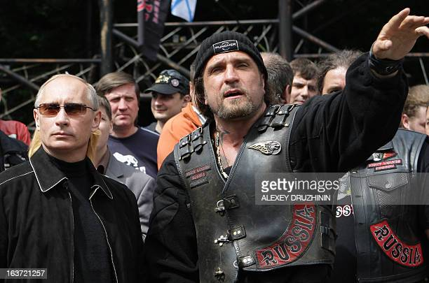 A picture taken on July 7 shows Vladimir Putin then Russian Prime Minister listening to the leader of Nochniye Volki biker group Alexander...