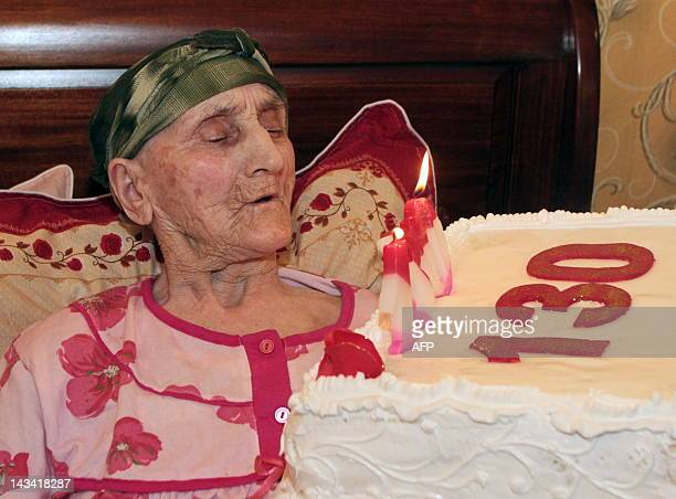 Picture taken on July 8 2010 shows Georgian woman Antisa Khvichava blowing out candles on her cake during her 130th birthday party in the village of...