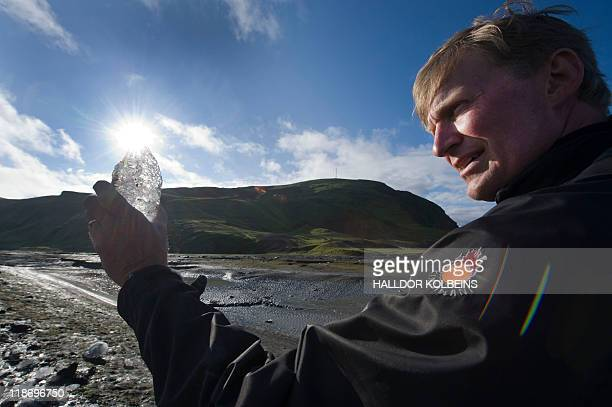 A picture taken on July 9 2011 shows geochemist Sigurour Reynir Gislason examining a sample of ice he collected on the partially collapsed and...