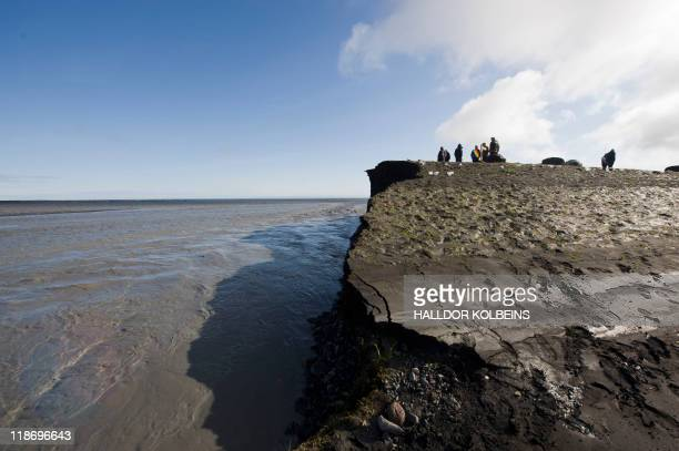A picture taken on July 9 2011 shows people standing on the partially collapsed road number 1 near Vik after a massive flood of meltwater poured out...