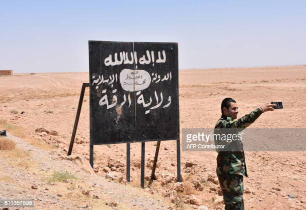 A picture taken on July 9 2017 shows a Syrian regime forces member taking a selfie with an Islamic State group billboard at the IthrayaRasafa highway...