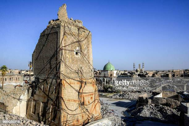 A picture taken on July 9 2018 shows a view of the base of the destroyed AlHadba leaning minaret with the dome of the destroyed AlNuri Mosque seen...