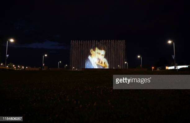 Picture taken on July 9, 2019 in Zagreb shows the fountains on the lawn outside the National and University Library , illuminated with an image of...