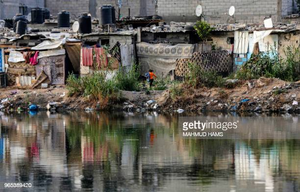 A picture taken on June 1 2018 shows a girl running past hovels near a sewage water pool at a poor neighbourhood in Gaza City