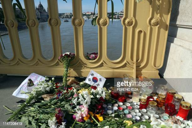 A picture taken on June 1 2019 in Budapest shows flowers candles and a SouthKorean flag on the Margit bridge over the Danube above the spot of a boat...