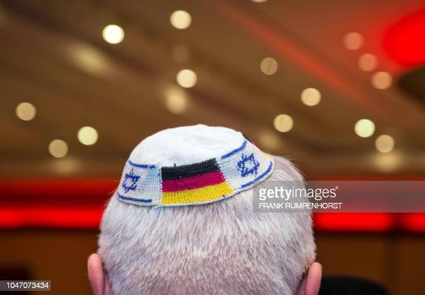 Picture taken on June 10 2014 in Frankfurt am Main western Germany shows a man wearing a Jewish kippa skullcap with the flags of Germany and Israel...