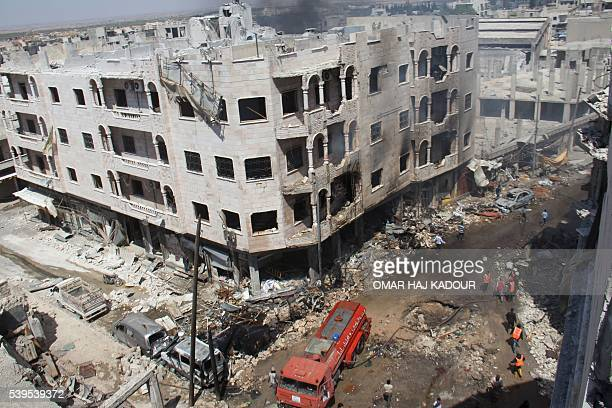 TOPSHOT A picture taken on June 12 2016 shows Syrian Civil Defence members known as the White Helmets gather at a site following air strikes on the...