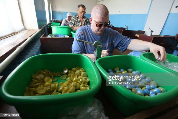 A picture taken on June 12 2017 shows partially sighted people putting disposable shoe covers into capsules in a factory in Donetsk The factory which...