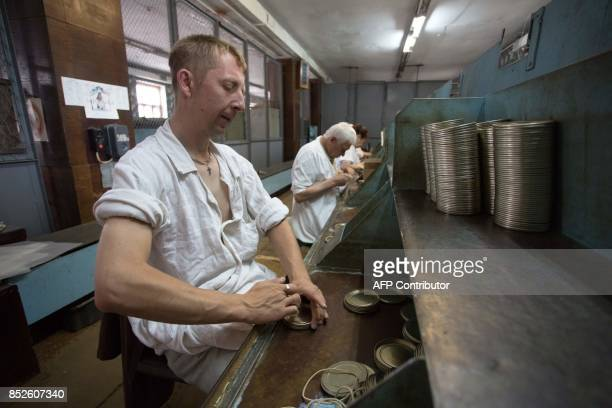 A picture taken on June 12 2017 shows partially sighted people assembling tin covers in a factory in Donetsk The factory which makes tin lids for...