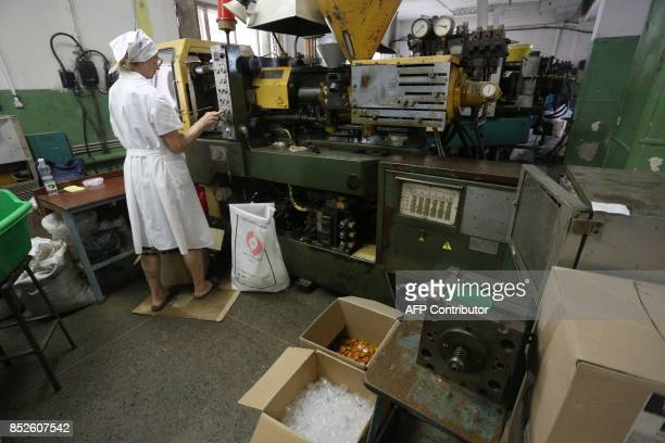 A picture taken on June 12 2017 shows partially sighted woman making capsules for disposable shoe covers in a factory in Donetsk The factory which...