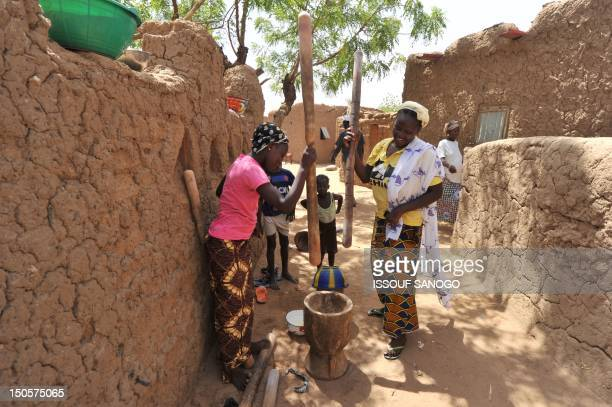 A picture taken on June 13 2012 shows women crushing cereals with a mortar and wooden pestle in GoromGorom northern Burkina Faso AFP PHOTO / ISSOUF...