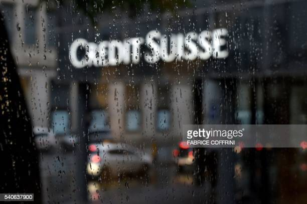 A picture taken on June 13 2016 shows a branch of Swiss banking giant Credit Suisse behind a window under the rain in Basel / AFP / FABRICE COFFRINI