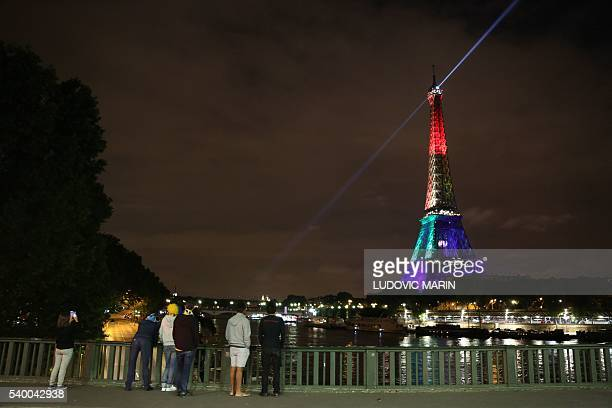 TOPSHOT A picture taken on June 13 2016 shows people looking at the Eiffel Tower in Paris as it is illuminated in rainbow colours to pay homage to...