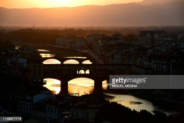 "Picture taken on June 13, 2019 shows the sunset over the ""Ponte Vecchio"" on the Arno river in Florence, Tuscany."