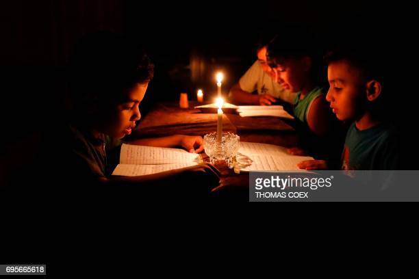 A picture taken on June 13 shows Palestinian children at home reading books by candle light due to electricity shortages in Gaza City Israeli Prime...