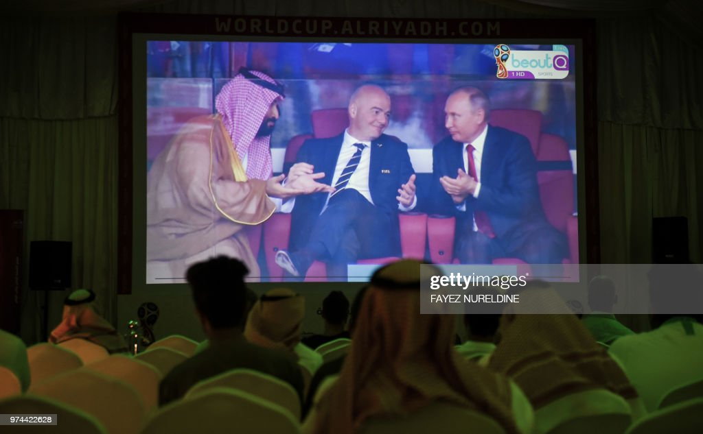 A picture taken on June 14, 2018 in a Saudi football fan tent in the capital Riyadh shows a projector showing the Russia 2018 World Cup Group A football match between Russia and Saudi Arabia, with a clip of Saudi Crown Prince Mohammed bin Salman (L) gesturing as he sits next to FIFA President Gianni Infantino (C) and Russian President Vladimir Putin (R).