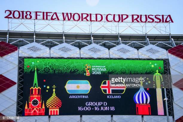 A picture taken on June 15 2018 shows a giant screen announcing tomorrow's match and the 2018 FIFA World Cup sign on top of the Spartak football...