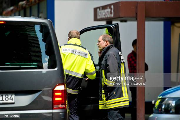 Picture taken on June 15 2018 shows an employee of the public health Robert Koch institute in front of an apartment building in Cologne's Chorweiler...