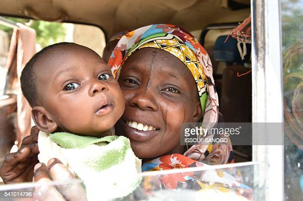 A picture taken on June 17 2016 shows a woman with her baby leaving the city of Bosso after recent attacks by Boko Haram Rotting bodies looted...