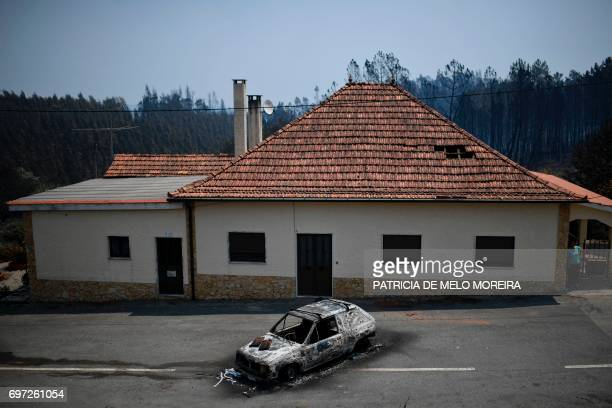 Picture taken on June 18, 2017 shows a car burnt in front of a house after a wildfire in Figueiro dos Vinhos. A wildfire in central Portugal killed...