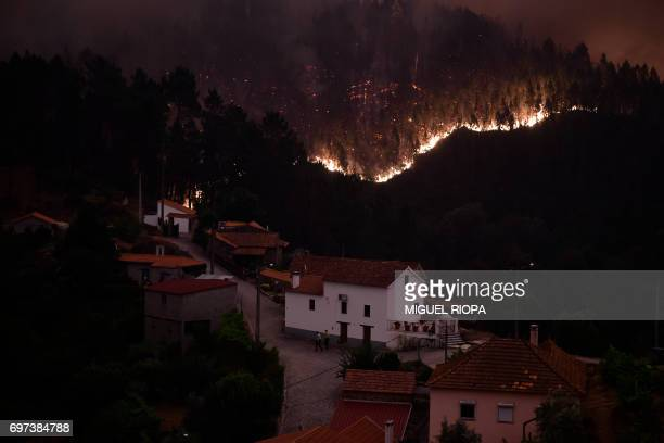TOPSHOT A picture taken on June 18 2017 shows flames and smoke during a wildfire near the village of Mega Fundeira Portugal declared three days of...