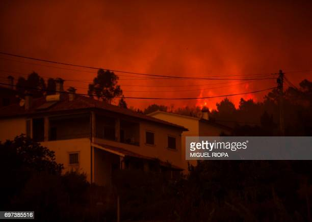 A picture taken on June 18 2017 shows flames burning vegetations in background of a house during a wildfire in the village of Derreada Cimeira...