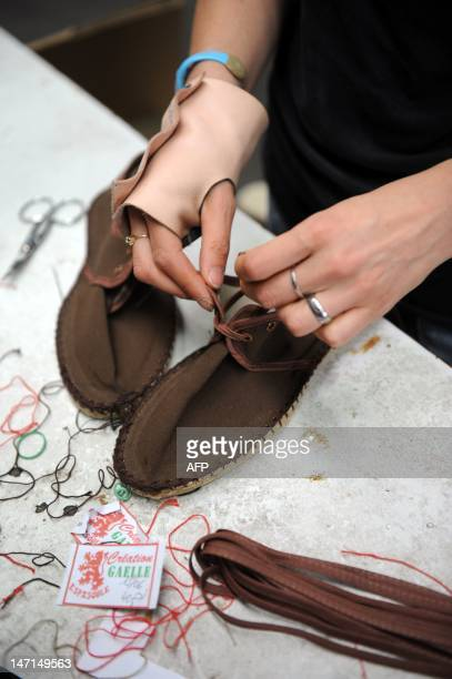 A picture taken on June 19 2012 in Mauleon the capital of the Soule region southwestern France shows an Espadrille being sewed at Megam Creation...
