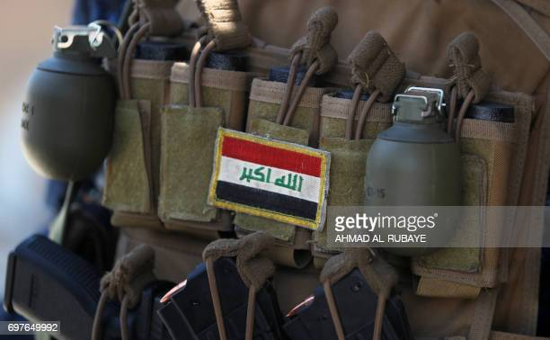Picture taken on June 19, 2017 shows an Iraqi flag patched on the ammunition belt of a member of the Iraqi forces among grenades and clips of...